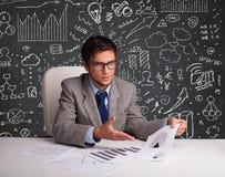 Homme d'affaires s'asseyant au bureau avec le plan et les icônes d'affaires Photos stock
