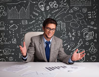 Homme d'affaires s'asseyant au bureau avec le plan et les icônes d'affaires Images libres de droits
