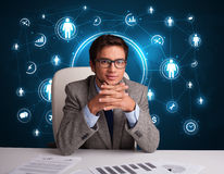 Homme d'affaires s'asseyant au bureau avec les graphismes sociaux de réseau Image libre de droits