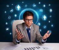 Homme d'affaires s'asseyant au bureau avec les graphismes sociaux de réseau Photographie stock libre de droits