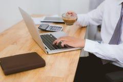 Homme d'affaires s'asseyant au bureau ayant une pause-café, il est Images stock