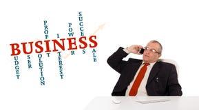 Homme d'affaires s'asseyant au bureau et faisant l'appel téléphonique avec le clou de mot Photo stock