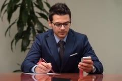 Homme d'affaires s'asseyant au bureau signant un contrat Images libres de droits