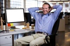 Homme d'affaires s'asseyant avec des mains derrière la tête par le bureau Images libres de droits
