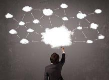 Homme d'affaires s'asseyant avec la technologie de nuage au-dessus de sa tête Photographie stock libre de droits