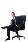 Homme d'affaires s'asseyant dans la présidence noire de bureau Image stock