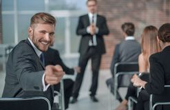 Homme d'affaires s'asseyant dans la salle de conférence, se dirigeant à vous Photographie stock libre de droits