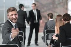 Homme d'affaires s'asseyant dans la salle de conférence, se dirigeant à vous Image stock