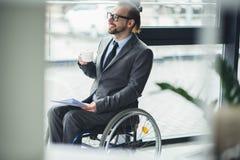 Homme d'affaires s'asseyant dans le fauteuil roulant tenant les documents et la tasse de cofee Photo libre de droits