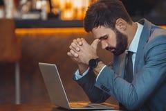 Homme d'affaires s'asseyant dans un fonctionnement de barre de centre d'affaires concerné images libres de droits