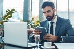 Homme d'affaires s'asseyant dans un restaurant de centre d'affaires utilisant le comprimé numérique concentré photo stock