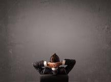 Homme d'affaires s'asseyant devant un mur avec l'espace de copie photo stock