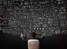 Homme d'affaires s'asseyant devant un tableau noir avec des diagrammes photo libre de droits