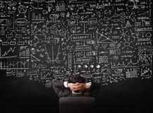 Homme d'affaires s'asseyant devant un tableau noir avec des diagrammes photos libres de droits