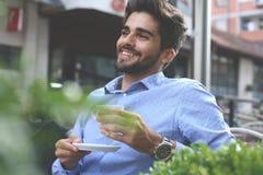 Homme d'affaires s'asseyant en café de rue et ayant la pause-café image stock
