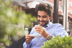 Homme d'affaires s'asseyant en café de rue et ayant le brea de café photo libre de droits
