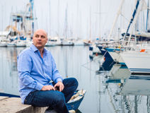 Homme d'affaires s'asseyant en les bateaux à voile et les yachts chers dans le C.A. photo libre de droits