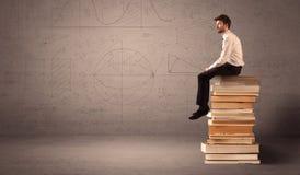 Homme d'affaires s'asseyant sur des livres Images stock