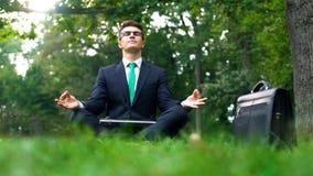 Homme d'affaires s'asseyant sur l'herbe dans la forêt et méditant après jour assidu image libre de droits