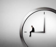 Homme d'affaires s'asseyant sur l'horloge Image stock