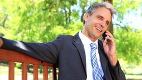 Homme d'affaires s'asseyant sur le banc de parc parlant au téléphone banque de vidéos