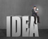 Homme d'affaires s'asseyant sur le dessus 3D du mot IDÉE avec le comprimé et l'ampoule Photos libres de droits