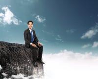 Homme d'affaires s'asseyant sur le dessus d'une haute montagne Photos libres de droits