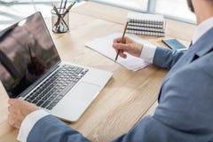 Homme d'affaires s'asseyant sur le lieu de travail avec les papiers et l'ordinateur portable dans le bureau Image libre de droits