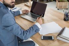 Homme d'affaires s'asseyant sur le lieu de travail avec les papiers et l'ordinateur portable dans le bureau Image stock