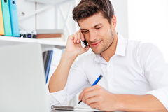 Homme d'affaires s'asseyant sur le lieu de travail et parlant au téléphone portable photo stock
