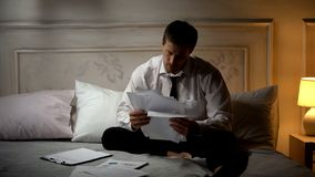 Homme d'affaires s'asseyant sur le lit parmi des papiers, déçus par le démarrage infructueux photo stock