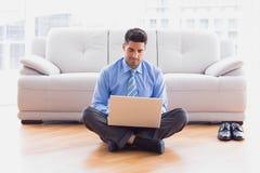 Homme d'affaires s'asseyant sur le plancher utilisant l'ordinateur portable Photo stock