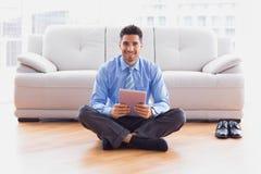 Homme d'affaires s'asseyant sur le plancher utilisant le PC de comprimé souriant à l'appareil-photo photo stock
