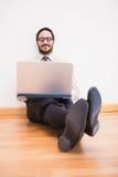 Homme d'affaires s'asseyant sur le plancher utilisant son ordinateur portable Photographie stock