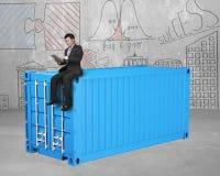 Homme d'affaires s'asseyant sur le récipient de cargaison 3d bleu Image libre de droits