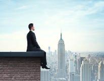 Homme d'affaires s'asseyant sur le toit photographie stock