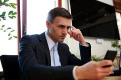 Homme d'affaires s'asseyant sur son lieu de travail Photographie stock