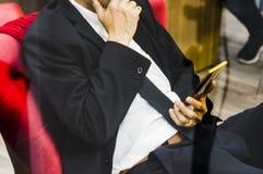 Homme d'affaires, s'asseyant sur une chaise rouge de velours, screenshots de smartphone de vue, gestes, fond courant de diagramme image stock