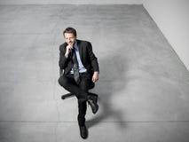 Homme d'affaires s'asseyant sur une présidence de bureau photo stock