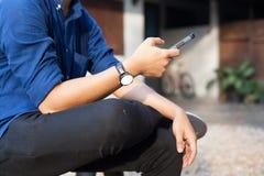 Homme d'affaires s'occupant des affaires au téléphone portable intelligent devant la maison paisible dans la campagne rurale Bure images libres de droits