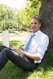 Homme d'affaires sûr avec l'ordinateur portable en parc Image libre de droits