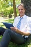 Homme d'affaires sûr avec le comprimé numérique en parc Photographie stock libre de droits