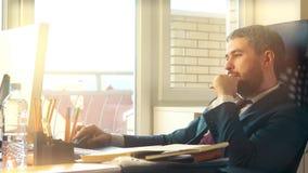 Homme d'affaires sûr de sourire travaillant sur son ordinateur au bureau vidéo 4K banque de vidéos