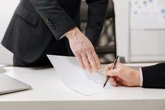 Homme d'affaires sûr signant le document important dans le bureau photographie stock