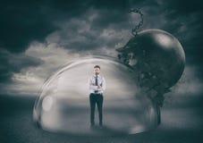 Homme d'affaires sans risque à l'intérieur d'un dôme de bouclier pendant une tempête qui le protège contre une boule de destructi image stock