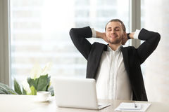 Homme d'affaires satisfaisant détendant sur le lieu de travail Photographie stock