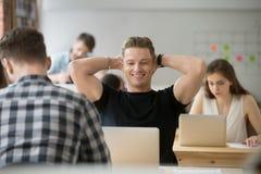 Homme d'affaires satisfaisant heureux tenant des mains derrière la tête regardant Photographie stock