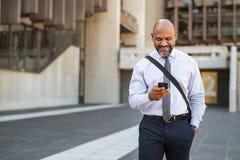 Homme d'affaires satisfaisant marchant tandis qu'utilisant le téléphone photographie stock libre de droits