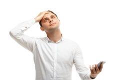 Homme d'affaires satisfaisant utilisant le téléphone tenant la tête Photographie stock libre de droits