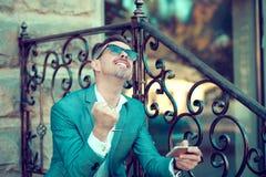 Homme d'affaires satisfait avec le téléphone sur la rue photographie stock libre de droits